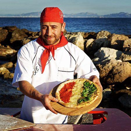 Portrait de ludovic bicchierai tenant une pizza napolitaine sur fond de méditéranée