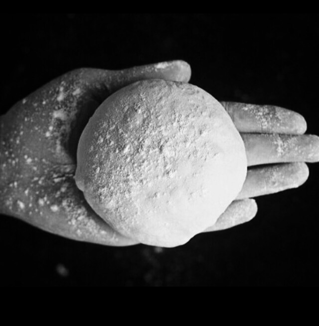 Photo noir et blanc d'une main tenant un boule de pâte à pizza par le Centre de Formation de pizzaiolo